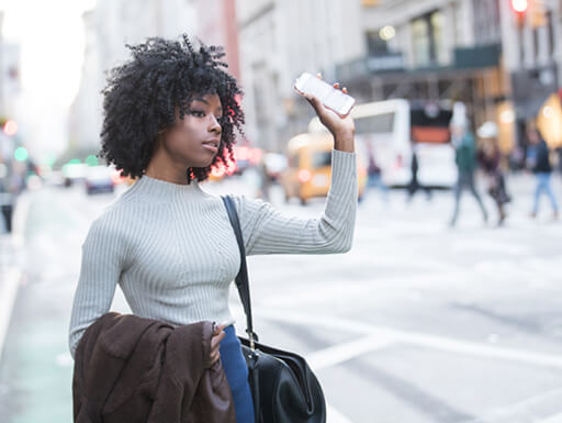 woman with curly curly Hair holding up phone
