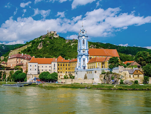 View of picturesque Durnstein town from across the Danube river with tree-covered mountains and a bright blue sky in the background on a sunny day near Vienna, Austria.