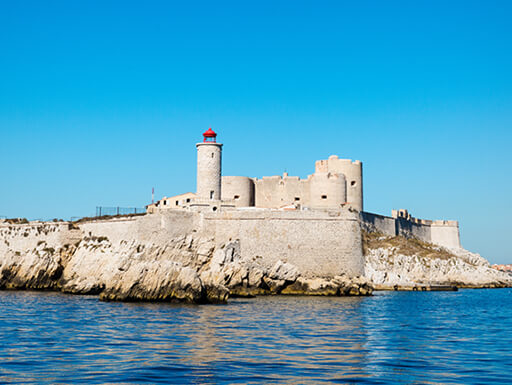 The former island prison of Chateau d'If near Marseille, France is an imposing stone fortress surrounded by clear water and a bright blue sky.