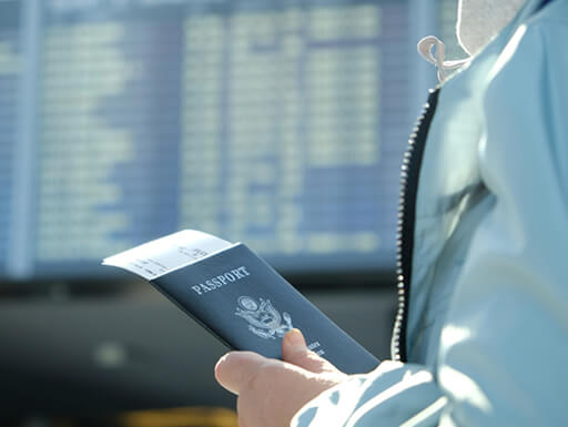 Close up of a woman holding her passport and walking through the airport after passing through passport control after using the Global Entry kiosk.