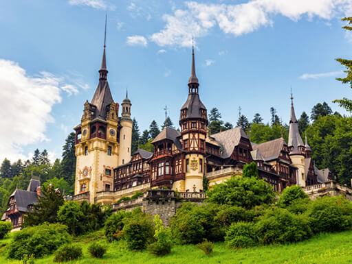 A view from below Peles Castle near Sinaia, Romania with gold and brown siding surrounded by lush greenery.