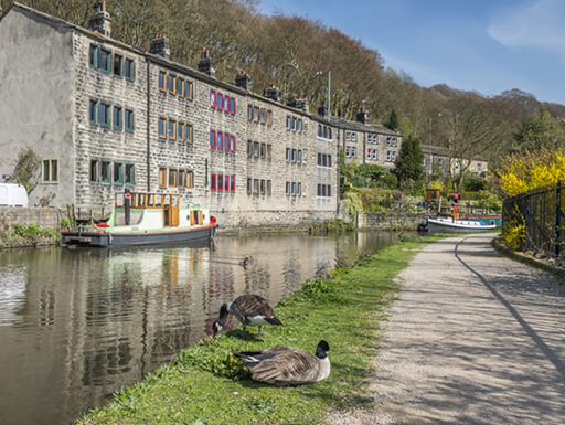 View of a slow moving canal and nearby building with rainbow-colored windows in Hebden Bridge, England.