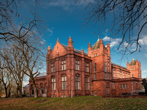 View of the Whitworth Art Gallery from behind trees on a crisp autumn evening in Manchester, England.