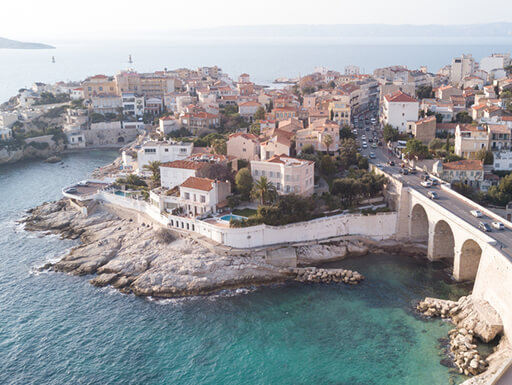 An aerial view of a section of La Corniche, Marseille shows the roadway and bridge and white buildings with red roofs built right up to the edge of the rocky coastline.
