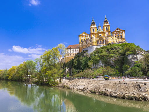 View of the Danube River overlooked by the ornate Stift Melk Abbey on a bright, sunny day near Vienna, Austria.