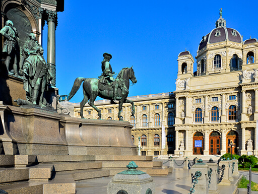 A street-level view of the iconic Museum Quarter, with ornate buildings and bronze statues, on a bright, sunny day in Vienna, Austria