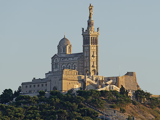 Marseille's Notre-Dame de la Garde, an ornate church drenched in the late afternoon sun, is situated above the entire city of Marseille.