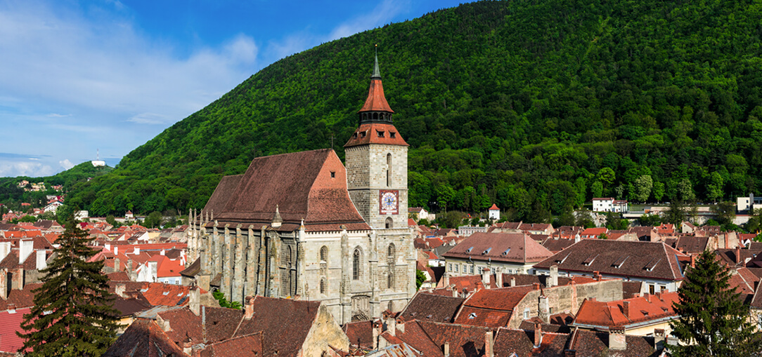 Arial view of Brasov in Romania with a Gothic Black Church and other stone buildings with red roofs nestled between lush green hills.