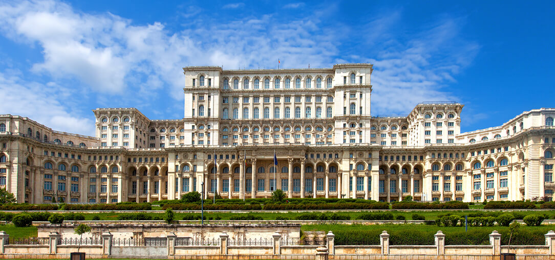 The Palace of Parliament, which has 1,000 rooms and is one of the biggest buildings of its kind in the world, seen in Bucharest, Romania under a bright blue sky on a summer day.