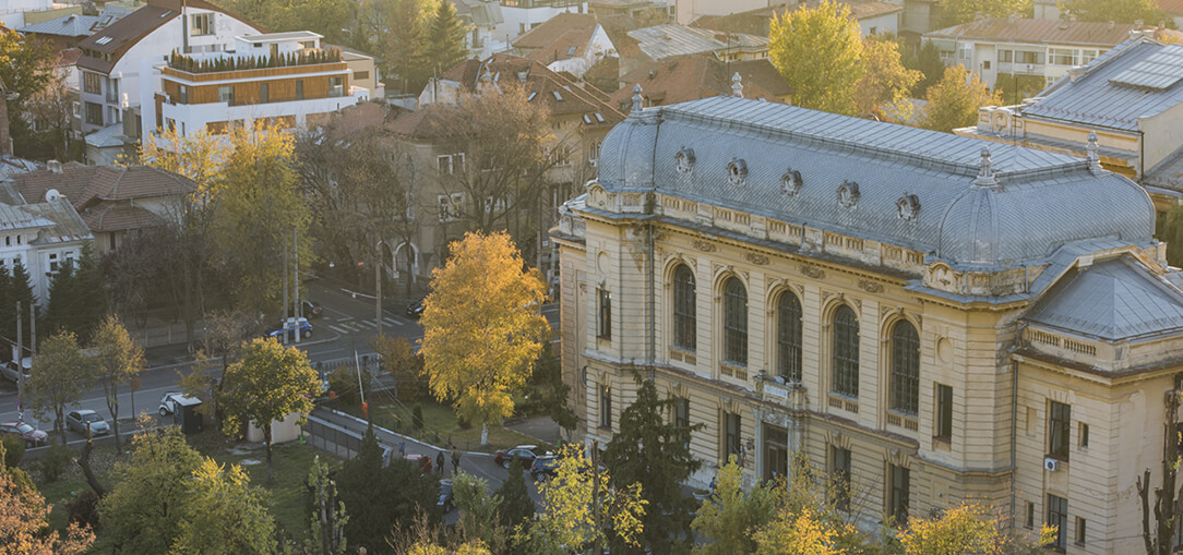 An aerial view of the Cotroceni neighborhood in Bucharest, Romania shows beautiful, old buildings and architecture surrounded by trees on a late afternoon.