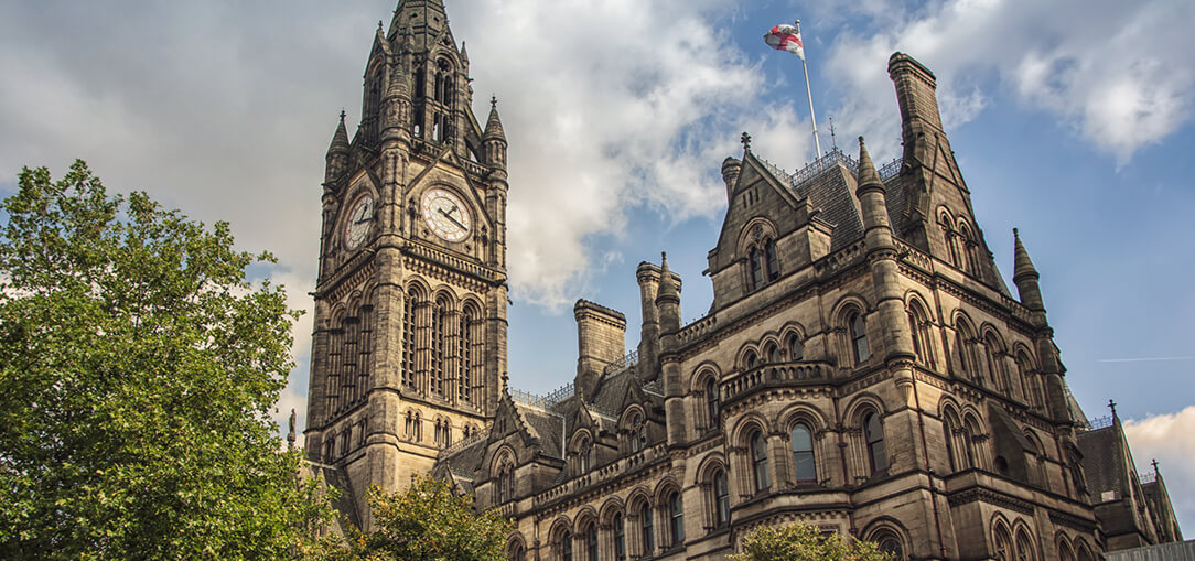 View from of the Manchester Town Hall in Albert Square with a clock tower and the British flag flying on a partly cloudy day in summer in Manchester, UK.