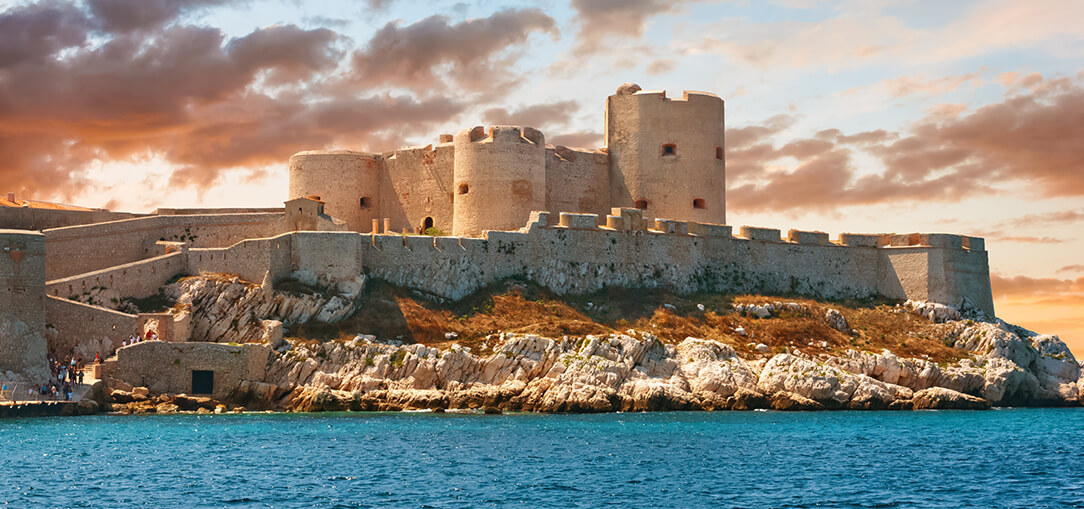 Chateau d'If, off the coast of Marseille, France is a stone fortress drenched in the evening sunlight during an early sunset on a partly cloudy day.