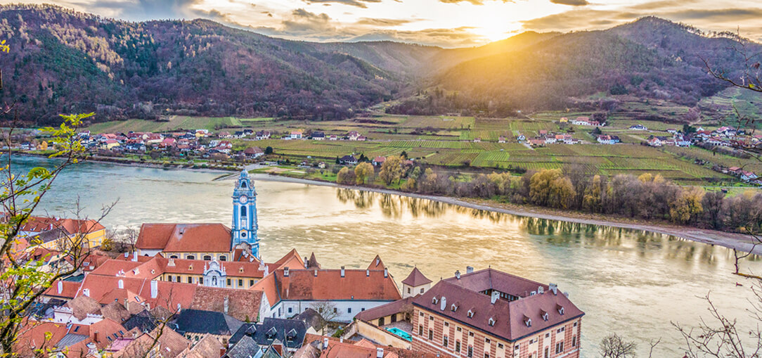 A panoramic view of Wachau Valley from Durnstein castle shows red-roofed buildings along the river with a mountain range in the background as the sun begins to set.