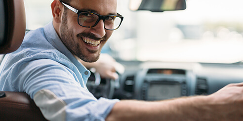 A rideshare driver smiles as he begins his driving route in his Hertz rental car on a beautiful day.