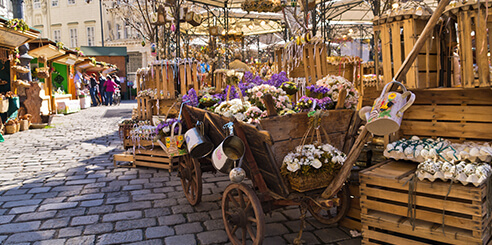 A street-level view of Am Hof square in Vienna shows carts full of colorful eggs ready for Easter on a morning in early spring.