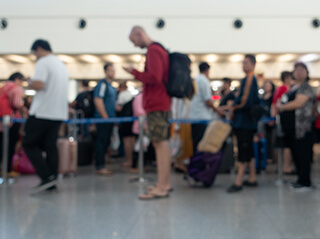 A line of passengers wait to pass through airport security on a busy day.