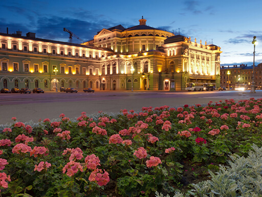 Mariinsky Theatre is illuminated in the late evening with flower beds lining the street nearby on a clear night in St. Petersburg, Russia.