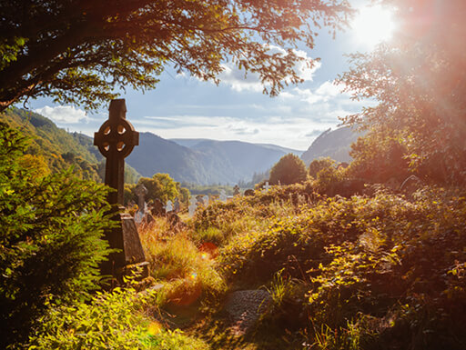 An old medieval Celtic cross is surrounded my greenery with a view of mountains in the far distance at Glendalough Monastery on a gorgeous sunny afternoon in County Wicklow, Ireland.