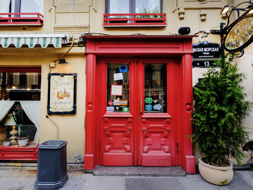 A vintage restaurant with bold, red doors and the menu posted outside in the city center of St. Petersburg, Russia.