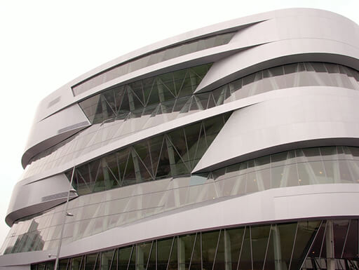 The exterior of the modern building, the Mercedes Benz Museum, in Stuttgart, Germany, on a cloudy day.
