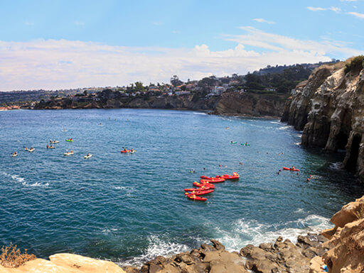 Red kayaks float on the water near the coastal caves at La Jolla, California, on a sunny afternoon.