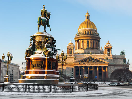 St. Isaac's Cathedral and the monument to Emperor Nicholas I are bathed in late-afternoon sunlight on a snow, winter day in St. Petersburg, Russia.
