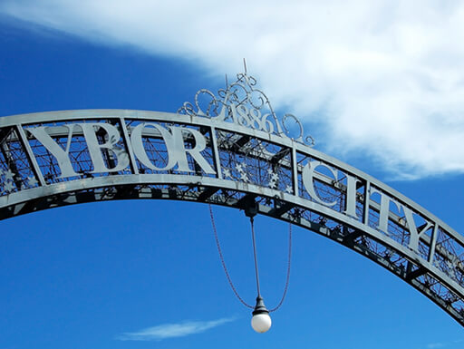 alt= The metal archway to Ybor City in Tampa, Florida, stands against a blue sky with white clouds.