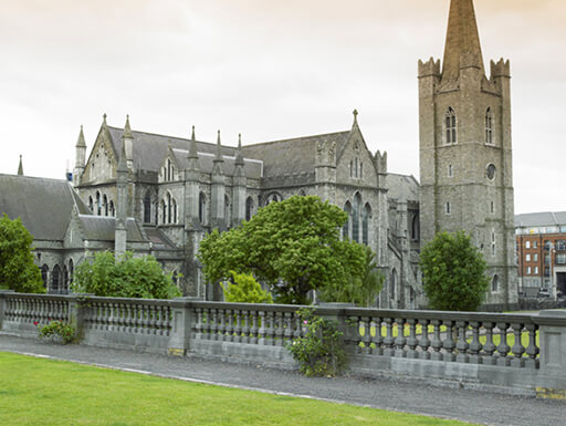 St. Patrick's Cathedral, the largest church in Ireland, is surrounded by green grass and short trees on a partly cloudy day in Dublin, Ireland.