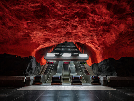The Solna Centrum Station of Stockholm's Metro system is an art installation, made to look like a red-skied forest with illuminated escalators for travelers.