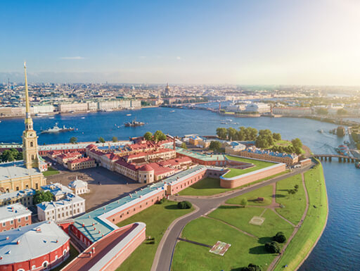 An aerial view of Peter and Paul Fortress in St. Petersburg shows colorful buildings and manicured landscape surrounded by water of the Neva River on a bright sunny day in Russia.