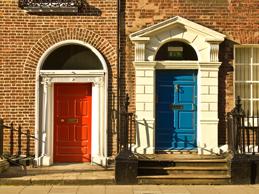 Gorgeous colorful red and blue doors on brown brick homes in Merrion Square on a sunny afternoon in Dublin, Ireland.