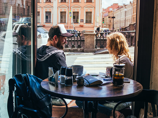 A view from inside a restaurant of a couple enjoying a meal on a cool day in St. Petersburg, Russia.