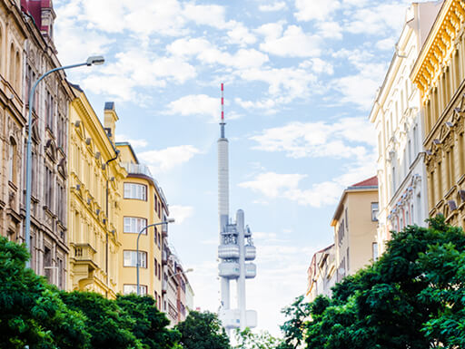 Television Tower in the Zizkov region of Prague is seen in the distance, with beautiful buildings and lush green trees lining the streets in the foreground on a sunny day in the capital of the Czech Republic.