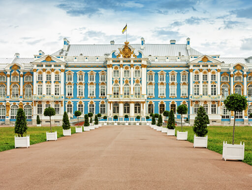 The Catherine Palace in St. Petersburg, Russia is a stately building with an aqua-blue exterior and perfectly landscaped lawn on a sunny summer day