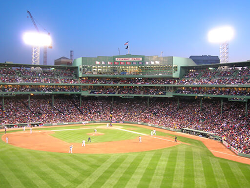 View of Fenway park at dusk with a beautifully manicured baseball field as fans fill the stadium.