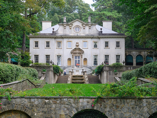Daytime view of the white Swan House estate in Atlanta surrounded by green foliage.