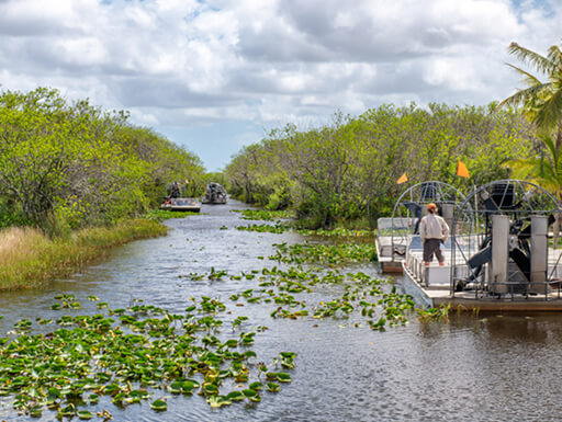 A man stands aboard an airboat in Everglades National Park, Florida on a partly cloudy afternoon.