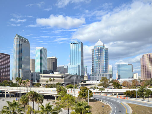 View of tall buildings and a highway in downtown Tampa skyline set against blue afternoon sky with white clouds.