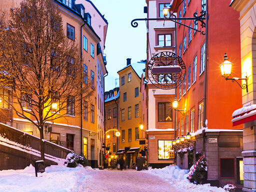 A snowy scene of a street-level view of Gamla Stan, Stockholm's Old Town on an early winter evening in Sweden.