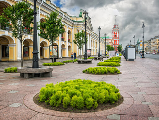 Green shrubs and trees along Nevsky Prospect near the Gostiny Dvor near colorful, ornate buildings on a cloudy day in St. Petersburg, Russia.