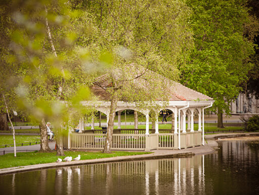 A quaint bandstand next to the lake in leafy St. Stephen's Green Park on a sunny afternoon in Dublin, Ireland.