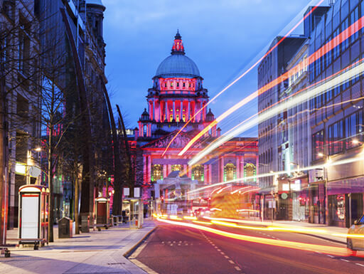 Belfast City Hall lit up at night as dusk falls on the busy city streets of Belfast, Ireland.