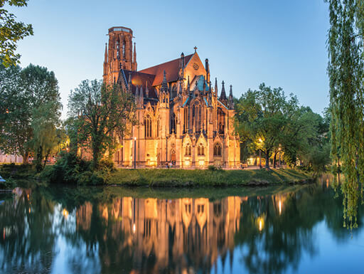 Stuttgart's St. John's Church and Fire Lake surrounded by lush green trees and grass just after sunset in the summer in Germany.