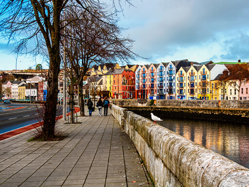The bank of the River Lee in Cork city center, lined with colorful shops and restaurants on a cold, winter day in County Cork, Ireland.