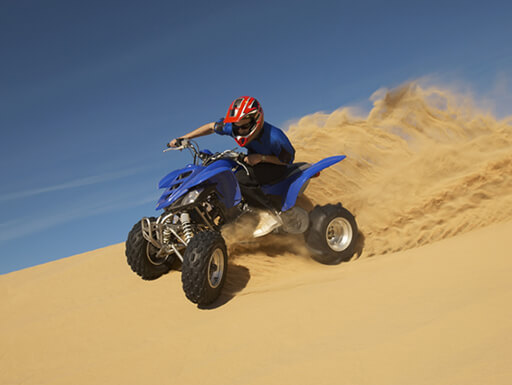 An ATV rider in a red helmet speeds across the sandy dunes outside of Las Vegas, Nevada, against a blue sky.