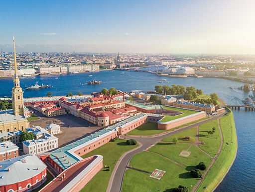 A bird's eye view of Peter and Paul Fortress in St. Petersburg shows the colorful buildings and walls, surrounded by pristine landscaping, right on the edge of the water on a sunny day in Russia.