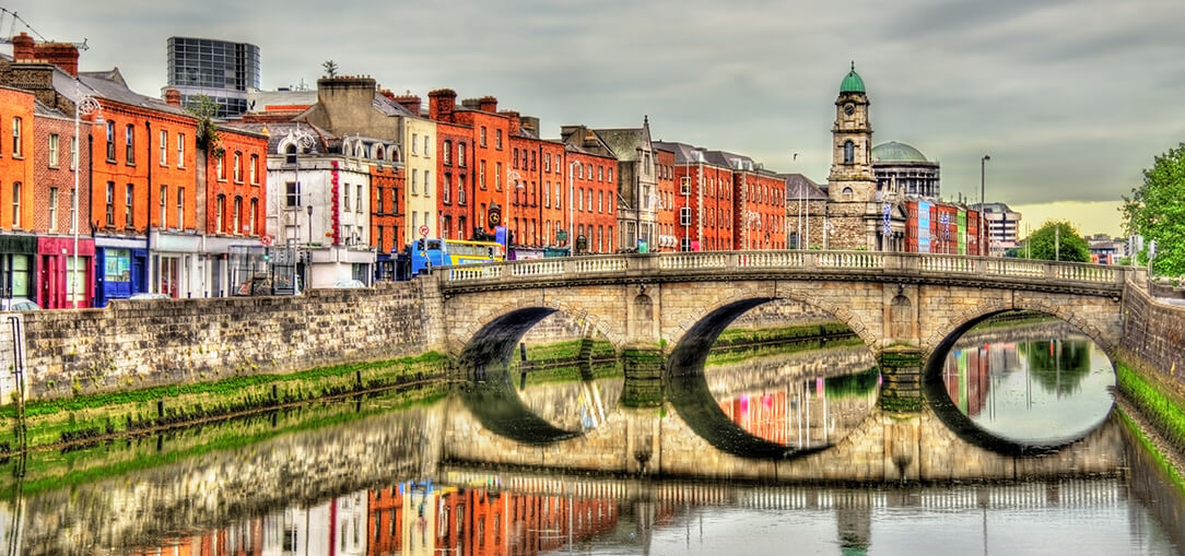 The old, stone Mellows Bridge is reflected in the River Liffey beside rows of brick buildings with colorful facades on a cloudy day in Dublin, Ireland.