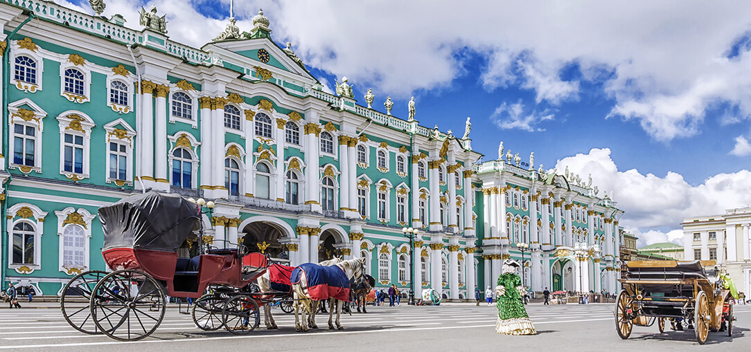 Bright red horse-drawn carriages outside the aqua Palace Square on a bright summer day in St. Petersburg, Russia.