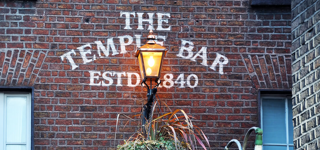 A sign is painted on a brick buildings in the famous Temple Bar area during the evening in Dublin, Ireland