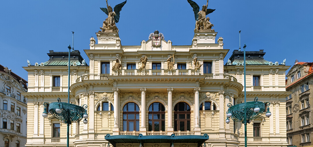 The historic Vinohrady Theater is an impressive piece of architecture adorned with columns and statues, seen on a sunny afternoon in Prague.